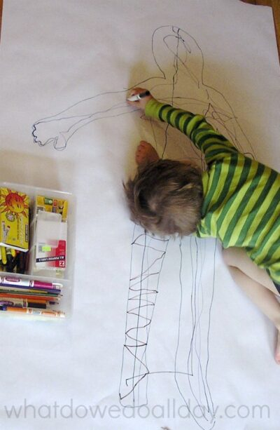 Body art project for kids with big paper on the floor.