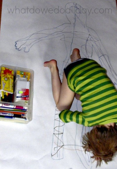 Full size body art project for kids on the floor.