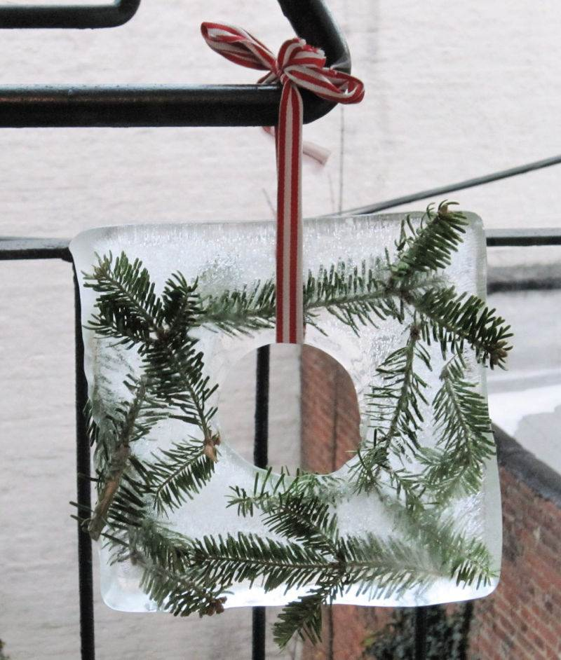 ice wreath with pine needles and red ribbon