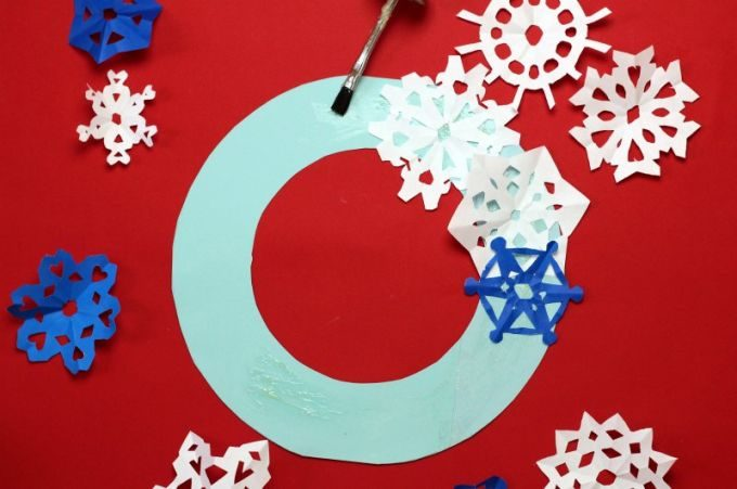 Glue snowflakes onto winter holiday wreath