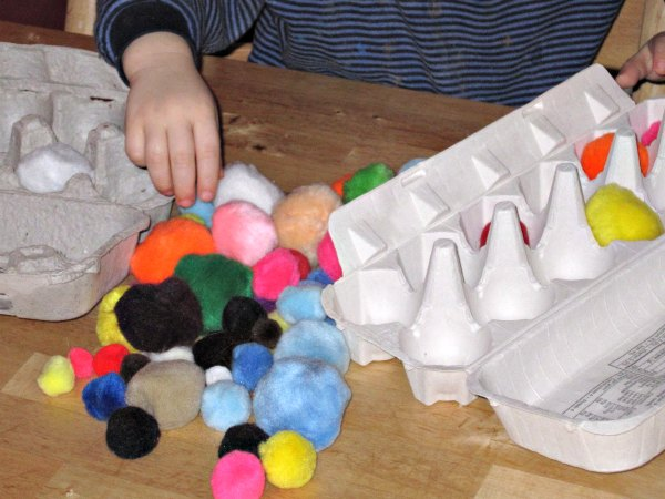 Toddler activity with egg cartons and pom poms
