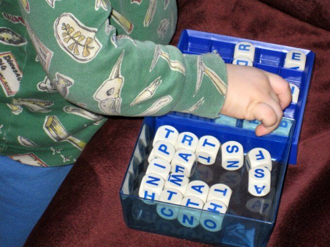 toddler playing with boggle game pieces