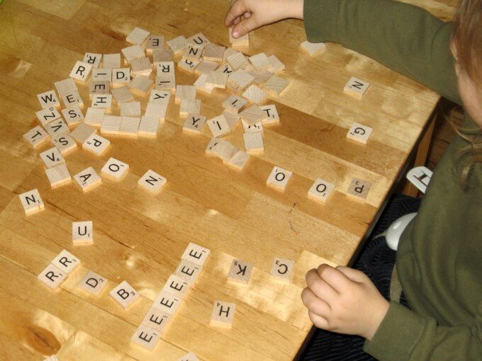toddler playing with scrabble pieces