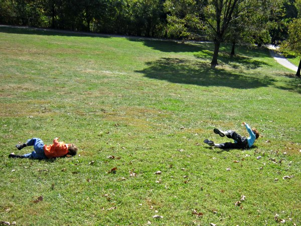 Classic outdoor activity for kids: rolling down the hill.