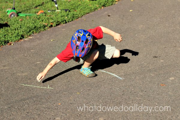 Drawing a scooter slalom outside with sidewalk chalk