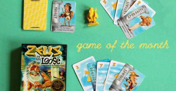 Family card game Zeus on the Loose showing cards fanned out, box and yellow Zeus figurine