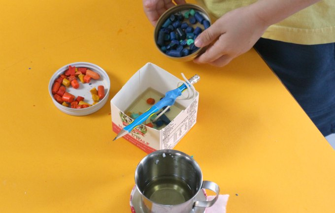 Adding crayon pieces to scented milk carton candles.