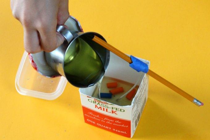 Pouring wax to make milk carton candles.
