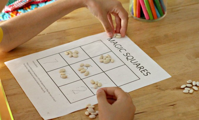 Playing a magic square math puzzle game.