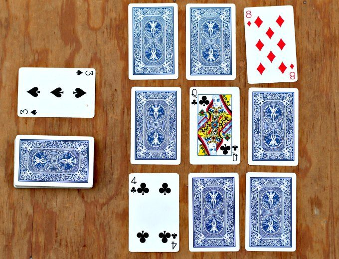 playing card layout of nine cards face up and face down with two extra stacks of cards, on a wooden surface