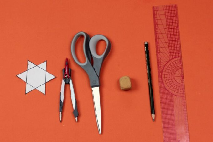 Supplies for drawing a 6 point star: scissors, compass, ruler and pencil