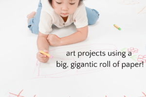 Child drawing on big piece of paper
