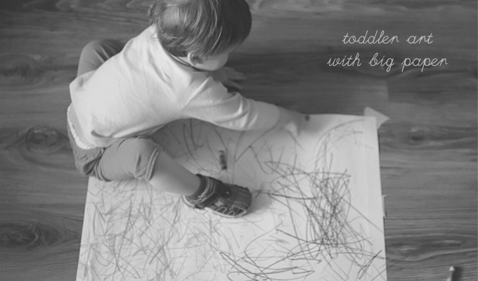 Toddler drawing on big roll of paper