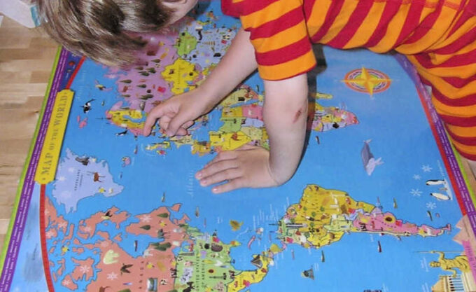 child looking at world map to learn geography