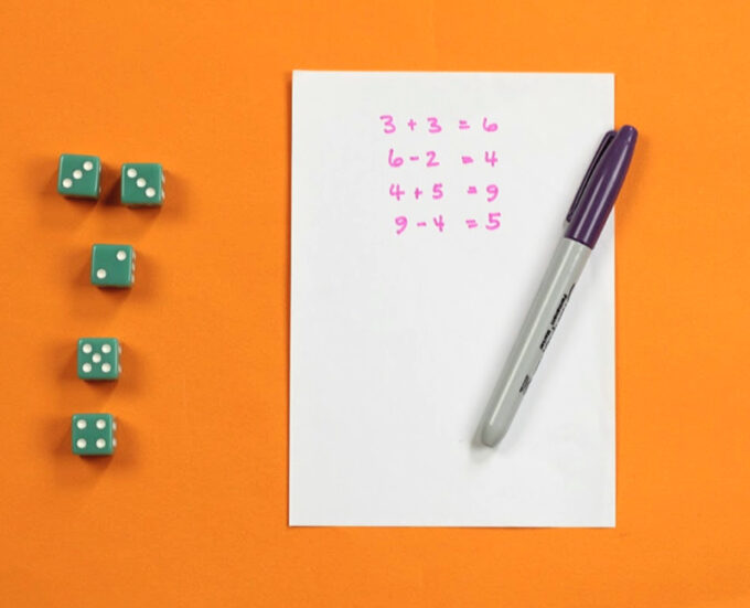 5 green dice and score sheet for addition and subtraction dice game