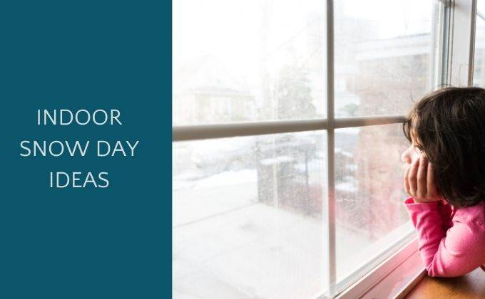 child looking out of window at snow