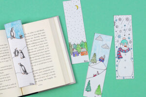 Winter scene bookmarks and open book on green background