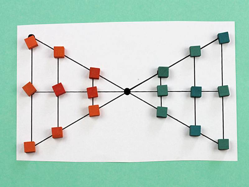lau kata kati game board in shape of two triangles connected at a single vertex with nine each green and orange square tokens on opposite triangles at points of intersection
