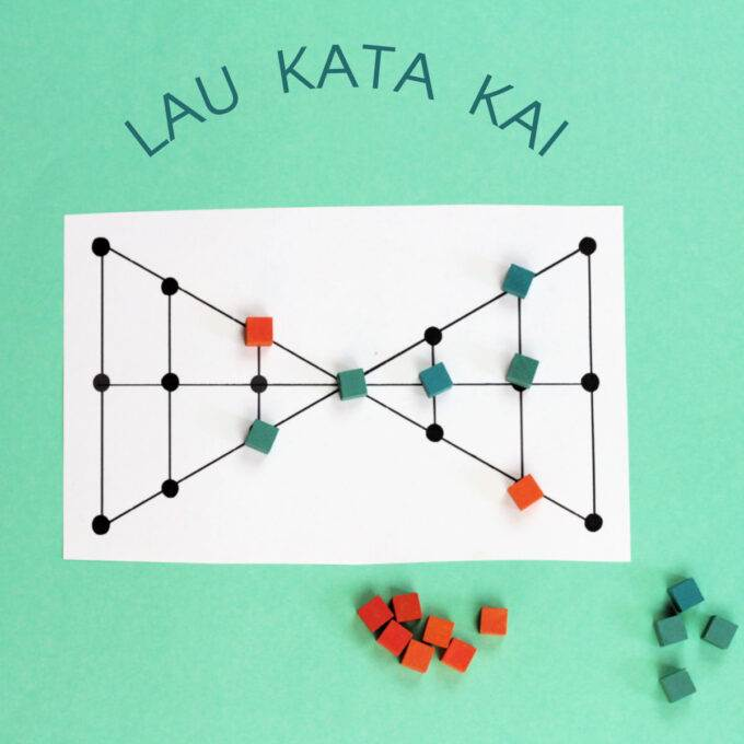 Lau Kata Kai game board in double triangle shape with some pieces on board, on green background
