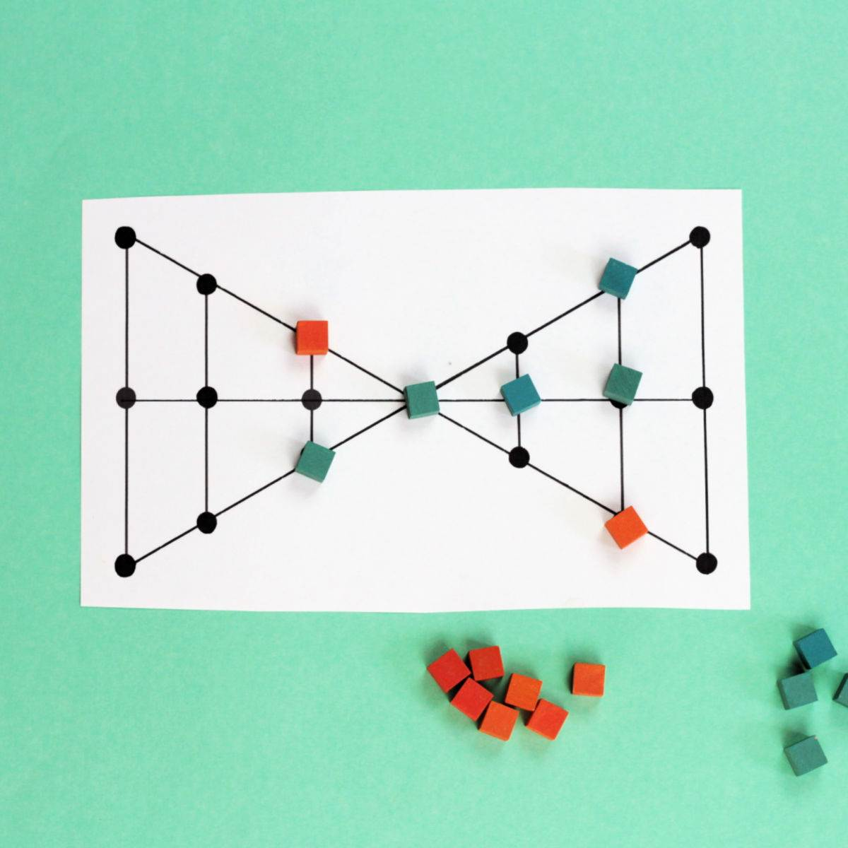lau kata kati game board in shape of two triangles connected at a single vertex with green and orange square tokens