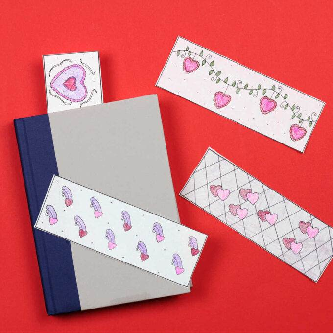 four colored valentine bookmarks on red background with one sticking out of grey book
