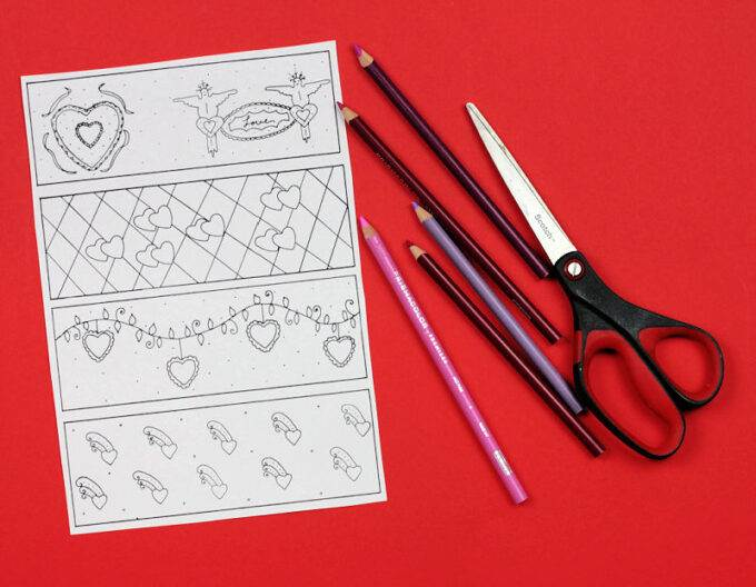 black and white coloring page showing four valentine bookmarks next to scissors and colored pencils
