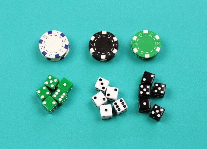 piles of white black and green casino chips and groups of five green, white and black dice