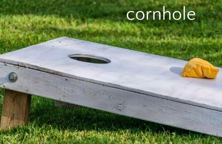 Cornhole board and yellow beanbag on lawn
