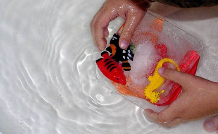 child's hands holding toy fish in ice block set in bath for child's activity